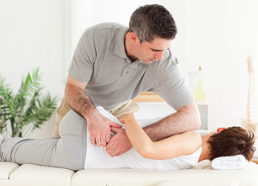 Chiropractor helping patient with back pain.