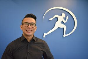 Dr. Newton Huynh – Chiropractor standing in front of Cornerstone Therapy and Wellness Logo