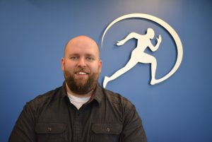 Dr. Thomas Iggulden – Chiropractor standing in front of Cornerstone Therapy and Wellness Logo